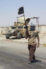 A fighter of the Islamic State of Iraq and the Levant (ISIL) stands guard at a checkpoint near Baiji.