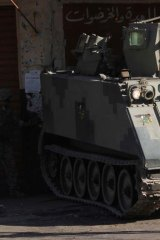 Tensions running high ... a Lebanese soldier runs in front of an armoured vehicle in Bab al-Tebbaneh.
