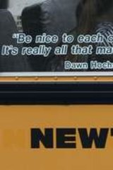 Children sit on a bus adorned with a quote from slain Sandy Hook school principal Dawn Hochsprung.