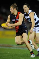 Geelong's Harry Taylor chases Essendon's Stewart Crameri.