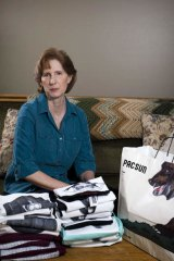 Judy Cox sits next to a stack of T-shirts with what she believes are pornographic designs Monday, Feb. 17, 2014, in Orem, Utah.