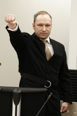 Anders Behring Breivik salutes as he enters the court on the first day of his trial.