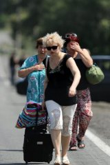 Fleeing residents of Shakhtersk carry their belongings in bags as they run to waiting cars on the outskirts of the city during heavy shelling.