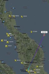 A flight tracker screenshot shows the point where MH370 went off radar.