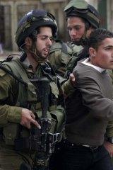 Hebron clash … Israeli soldiers seize a Palestinian boy.
