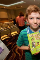 """Finn Prendergast, 7, from Taragindi, and Ned Naouri, 7, from Annerley, have their copies of """"Deadly D and Justice Jones - Making the Team"""""""