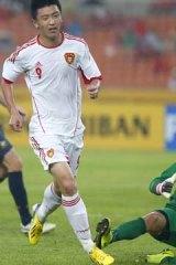 China's Yang Xu (front) runs after scoring a goal against Australia's Mark Birighitti.