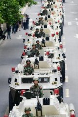 A convoy of armoured vehicles parades through Urumqi in a show of force on Friday, the day after a terrorist attack on a city market that has so far claimed the lives of 43 people.