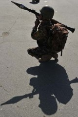 Under attack ... an Afghan National Army (ANA) soldier keeps watch near the scene of an attack in Kabul.