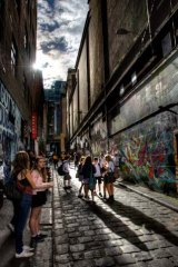 Ray of light: School children catch a bit of sun in Hosier Lane in the CBD.