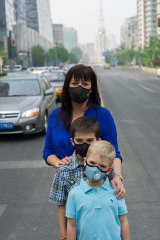 """Under wraps: Kristen McAnulty and sons Jacob and Ethan out on a day when the air quality is classified """"very unhealthy""""."""