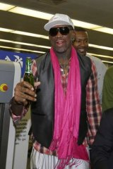 Former NBA player Dennis Rodman holds a bottle of beer as he arrives at the Beijing Capital International Airport to leave for Pyongyang in January.