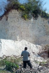Jaime Awe, head of the Belize Institute of Archaeology, looks at the damaged sloping sides of the Nohmul complex, one of Belize's largest Mayan pyramids.