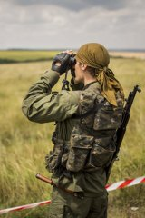 Russian separatists deny responsibility for the missile: A pro-Russia rebel surveys the area around the MH17 wreckage.