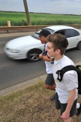 Students walk along busy Leakes Road.