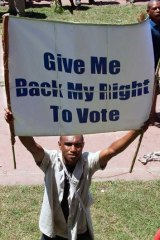 """""""We should expect the elections to be violent"""" ... a man demands suffrage as thousands of Papua New Guineans protest against the government's plan to delay national elections during a rally in Port Moresby on April 10, 2012."""