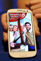 """A Facebook employee holds a phone that is running the new """"Home"""" program during an event at Facebook headquarters."""