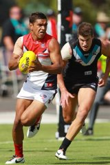 Neville Jetta of the Demons gets away from Paul Stewart of the Power.