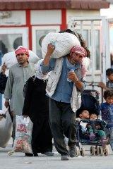Syrian refugees walk to cross into Turkey at Akcakale on Monday.