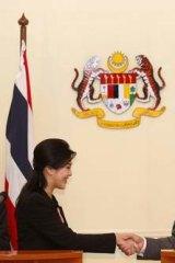 An uneasy alliiance ... Prime Minister Yingluck Shinawatra and her Malaysian counterpart Najib Razak shake hands.