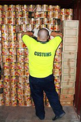 Cans of worms: An Australian Customs officer with some of the tomato cans containing ecstasy tablets in Melbourne in 2008.