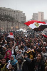 People wave flags as they gather in Cairo's Tahrir Square to celebrate the first anniversary of the revolution against Hosni Mubarak's regime.