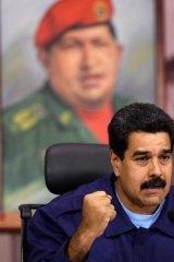 Defiant: Venezuelan President Nicolas Maduro speaks to the media in front of a portrait of his dead predecessor, Hugo Chavez.