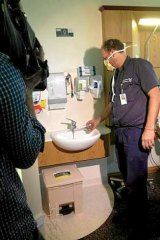 A hospital staffer tests the water temperature at the Wesley Hospital, Brisbane.