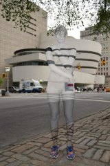 A model appears to blend into the background as she stands in front of the Guggenheim Museum in New York.