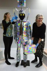 Disco-a-go-go: Alexandra Lucas and curator Glynis Jones dress a mannequin in the suit formerly worn by Peter Tully.