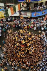 """Indian youth form a human pyramid to break the """"Dahi handi,"""" an earthen pot filled with curd, a part of the Hindu festival of Dahi Handi."""