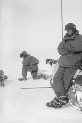 Xavier Mertz takes a photo of Douglas Mawson, while Belgrave Ninnis kneels in the background.