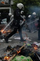 Police walk past burning debris in Istanbul's Cihangir district during the anniversary protests.