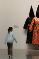 Young girl walks past a work titled <em>HHH</em> by artist Fiona Foley at the NGA in Canberra.