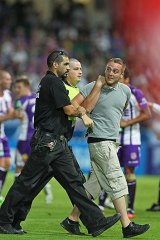 An over-enthusiastic fan is led off the pitch by security during Saturday night's game between the Perth Glory and Sydney FC.