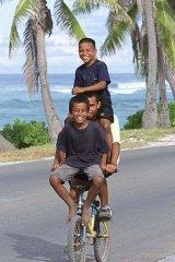 Nauruan boys share a bike ride on the island's main road.