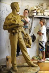 Queensland schoolboy Ronan Robinson watches Melbourne sculptor William Eicholtz put the finishing touches.