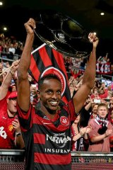 Youssouf Hersi holds the Premiers' Plate aloft after winning the semi-final against the Brisbane Roar on Friday.