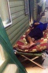 An asylum seeker sleeps outside to escape stifling heat.