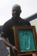 Johnson holds a cast of his footprint made after running on the track at the Seoul Olympic Stadium on Tuesday.