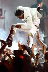 Crushing moment ... Singer Miguel leaping across the crowd during his performance at the Billboard Music Awards.
