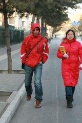 John Garnaut at work walking with Maya Li outside our compound.