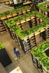 Green theme: The Naver library's bookshelves are laid out like a maze and topped  with hydroponic plants.
