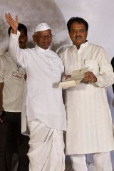 Anna Hazare waves as he accepts a letter on the agreement.