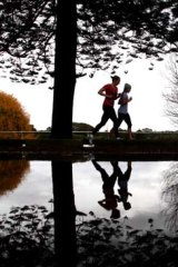 Slippery path ... joggers take to a gloomy Centennial Park in Sydney early yesterday.