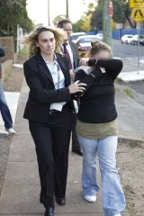 ''An underbelly of our society'' ... police escort one of the five suspects arrested yesterday in connection with a child prostitution ring in Sydney's south-west.