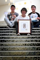 Harley Russo (centre) in 2014 aged 14 with his triplet brothers Cameron and Dylan. A combined family effort has seen Harley secure every first coin struck since 2013. But this year, the family is further down the line.