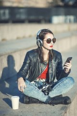 A hipster girl in leather jacket and glasses listening to music; could she be a Millennialoomer?