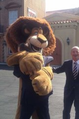 Alex the lion gives Treasurer Tim Nicholls a hug, but Premier Campbell Newman misses out, at Movie World.
