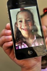 India Thomas shows the damage to her father's new iPhone when it was dropped on the road.